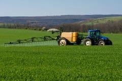 在一块麦田的拖拉机喷洒的杀虫剂 库存照片