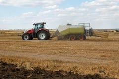 在一块麦田的运转的干草打包机与秸杆在天空中拂去灰尘 库存照片