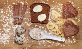 在一块黑面包和燕麦芯片和肉桂条和香蕉芯片的在桌上的鹌鹑蛋和曲奇饼 图库摄影
