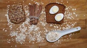 在一块黑面包和燕麦芯片的鹌鹑蛋和在桌上的一根肉桂条 免版税库存图片