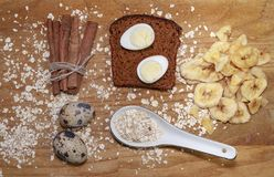 在一块黑面包和燕麦芯片的鹌鹑蛋和在桌上的肉桂条和香蕉芯片 库存图片