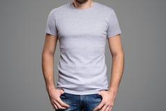 在一块年轻人模板的灰色T恤杉 灰色背景 免版税库存照片