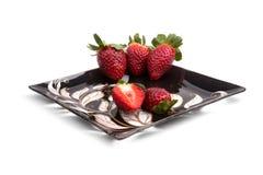 在一块黑发光的板材的草莓 免版税库存照片