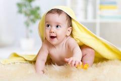 在一块戴头巾毛巾下的滑稽的婴孩孩子在浴以后 库存照片