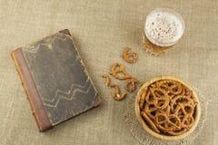 在一块玻璃和一本书的啤酒在桌上 与盐的酥脆麦子秸杆 堆椒盐脆饼棍子 免版税库存照片
