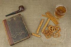 在一块玻璃和一本书的啤酒在桌上 与盐的酥脆麦子秸杆 堆椒盐脆饼棍子 库存照片