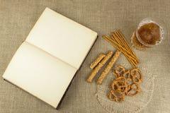 在一块玻璃和一本书的啤酒在桌上 与盐的酥脆麦子秸杆 堆椒盐脆饼棍子 免版税库存图片