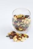 在一块玻璃和堆的混杂的坚果在地板上 免版税库存照片