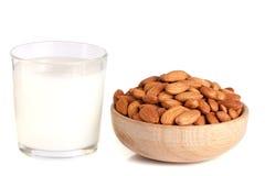 在一块玻璃和杏仁的杏仁牛奶在白色背景隔绝的一个木碗 免版税图库摄影