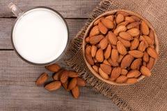 在一块玻璃和杏仁的杏仁牛奶在老木背景的一个碗 顶视图 库存照片