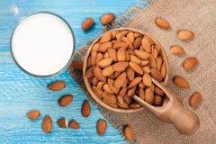 在一块玻璃和杏仁的杏仁牛奶在蓝色木背景的一个碗 顶视图 库存图片