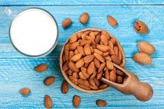 在一块玻璃和杏仁的杏仁牛奶在蓝色木背景的一个碗 顶视图 免版税库存照片