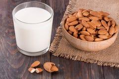 在一块玻璃和杏仁的杏仁牛奶在黑暗的木背景的一个碗 免版税库存图片