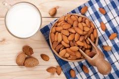 在一块玻璃和杏仁的杏仁牛奶在轻的木背景的一个碗 顶视图 库存照片