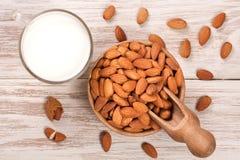 在一块玻璃和杏仁的杏仁牛奶在轻的木背景的一个碗 顶视图 免版税库存图片