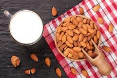 在一块玻璃和杏仁的杏仁牛奶在黑石背景的木碗 顶视图 库存图片