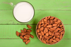 在一块玻璃和杏仁的杏仁牛奶在绿色木背景的一个碗 顶视图 库存图片
