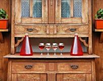 在一块玻璃和瓶的家庭红葡萄酒在葡萄酒木碗柜的上面 免版税库存图片