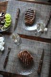 在一块玻璃板烤的牛排 杯酒,菜 免版税库存图片