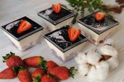 在一块玻璃的乳蛋糕点心用在白色背景的新鲜的草莓 免版税库存图片