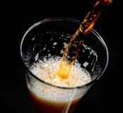 在一块玻璃的倾吐的冷的泡沫似的啤酒在黑背景 免版税库存图片