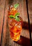 在一块玻璃的冷的芬芳茶在木背景,薄荷叶 免版税库存照片