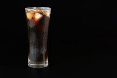 在一块玻璃的可乐水与冰 库存照片