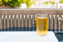 在一块玻璃的啤酒在翻斗车的泡沫箱子 免版税库存图片