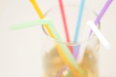 在一块玻璃的多彩多姿的管与一份黄色饮料 库存图片