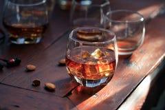 在一块玻璃的威士忌酒波旁酒与在木桌背景的冰 免版税库存照片