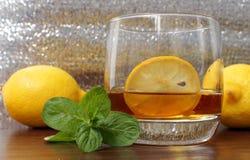 在一块玻璃的威士忌酒用柠檬 库存照片