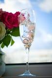 在一块玻璃的婚戒用香槟 库存照片