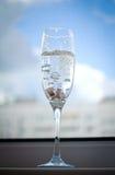 在一块玻璃的婚戒用香槟 图库摄影