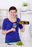 在一块玻璃的少妇倾吐的白葡萄酒在她的厨房里 免版税库存照片