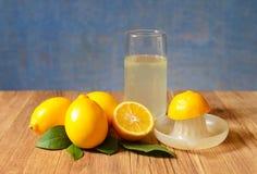在一块玻璃的新近地被紧压的柠檬汁用成熟柠檬 库存图片