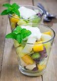 在一块玻璃的新鲜的健康水果沙拉与纯奶油 免版税库存图片