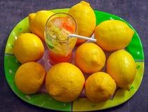 在一块玻璃的新鲜的柠檬水与切片柠檬、杏子和薄菏 免版税库存图片