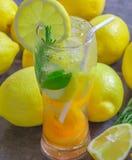 在一块玻璃的新鲜的柠檬水与切片柠檬,杏子,铸造  库存图片