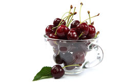 在一块玻璃的新鲜的甜樱桃在白色背景 免版税库存图片