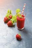 在一块玻璃的新鲜的草莓圆滑的人在黑背景 库存照片