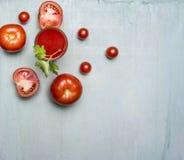 在一块玻璃的新鲜的西红柿汁与秸杆,与绿色叶子,切好的蕃茄在边界,正文木rusti附近传播了 图库摄影