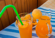 在一块玻璃的杏子汁与秸杆和投手 免版税库存照片