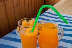 在一块玻璃的杏子汁与秸杆和投手 免版税库存图片