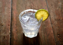 在一块玻璃的柠檬水与切片在木背景的柠檬 免版税库存图片