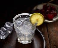 在一块玻璃的柠檬水与切片柠檬,果子板材在背景中 免版税图库摄影