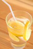 在一块玻璃的柠檬水在木桌上 免版税库存图片