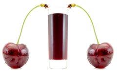 在一块玻璃的樱桃汁在白色隔绝的大樱桃的边 免版税库存照片