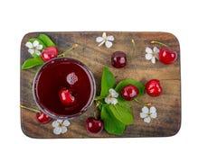 在一块玻璃的樱桃汁用新鲜的莓果和花 库存图片