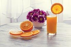 在一块玻璃的橙汁与花花束  免版税库存图片