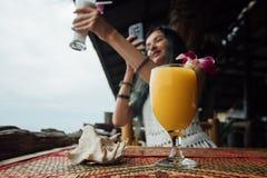 在一块玻璃的橙色芒果汁与在海壳旁边的一朵花在前景 免版税图库摄影